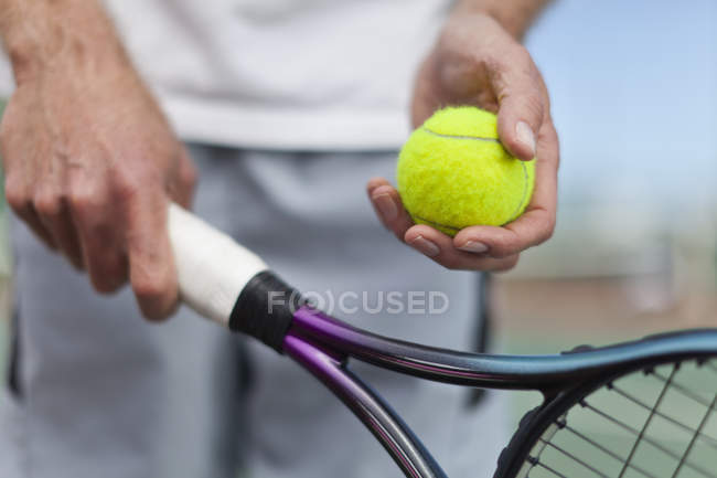 Older man holding tennis ball and racket, cropped shot — Stock Photo