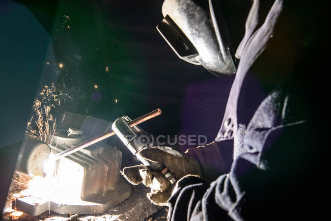 Worker cutting metal with electric arc in foundry — Stock Photo