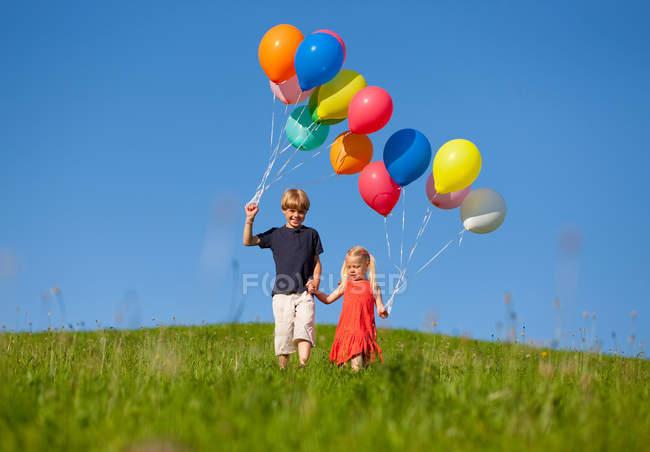 Enfants avec des ballons colorés dans l'herbe — Photo de stock
