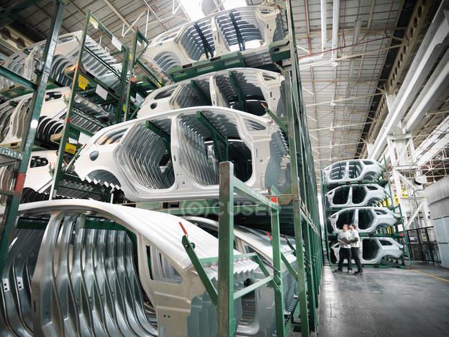 Ingegneri con parti di auto pressate in fabbrica di auto — Foto stock