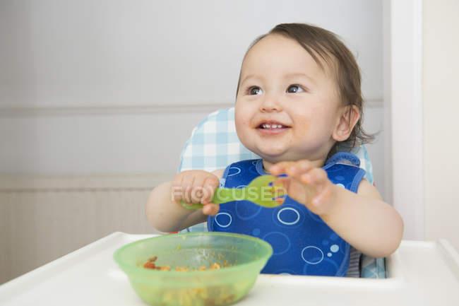 Мальчик ест детское питание в кухонном стульчике — стоковое фото