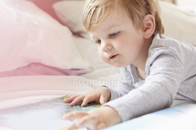 Head and shoulders of boy on bed lying on front looking at storybook — Stock Photo