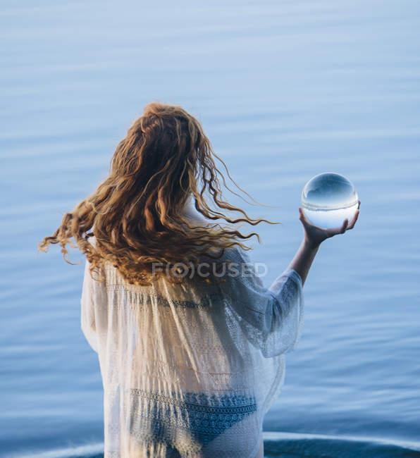 Вид сзади молодой женщины с длинные красные волосы стоя в озере Холдинг хрустальный шар — стоковое фото