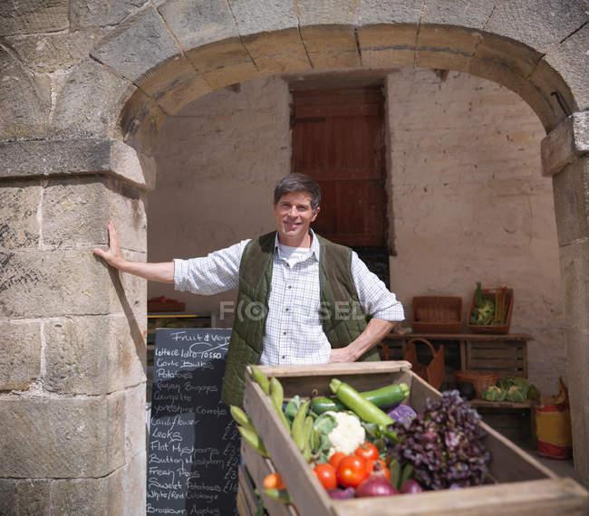 Портрет фермера, продающего органические овощи под аркой на ферме — стоковое фото