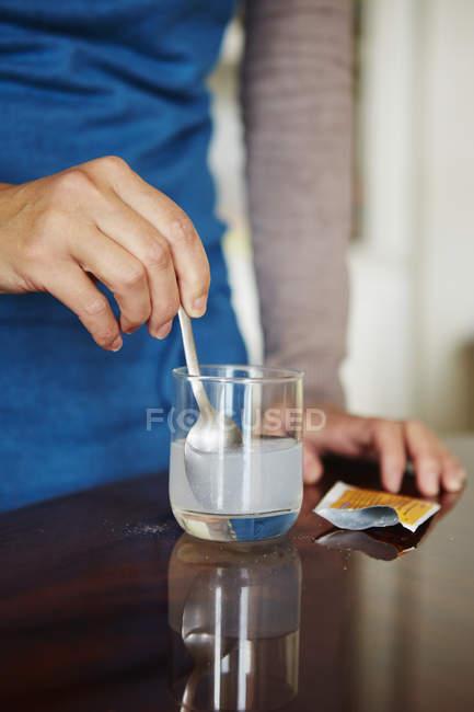 Jeune femme mélange de médicaments solubles dans l'eau du sachet, en verre d'eau — Photo de stock