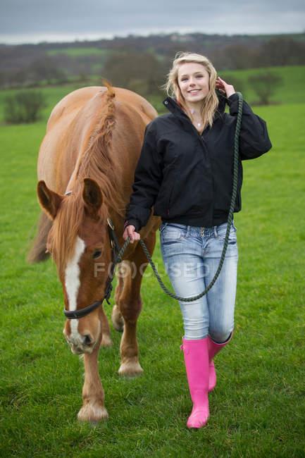 Teenage girl walking horse in field — Stock Photo