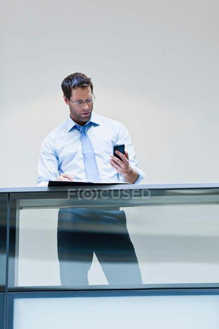 Homme d'affaires utilisant un smartphone sur le balcon — Photo de stock