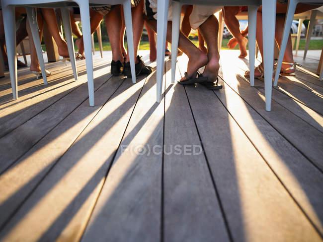 Molte gambe sotto ombre di colata di tavolo — Foto stock
