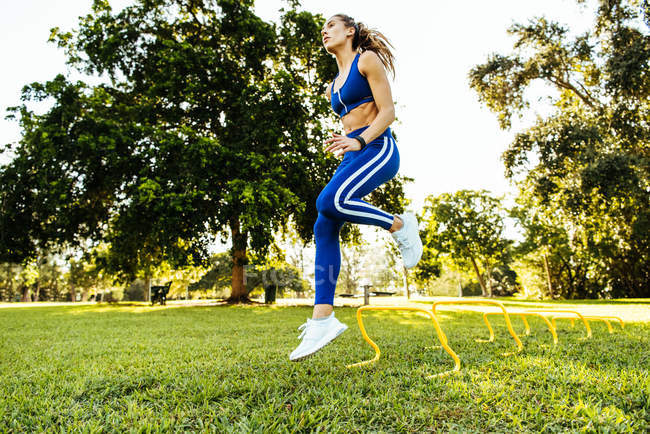 Young woman training, jumping agility hurdles in park — Stock Photo