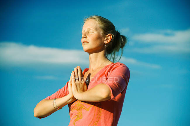 Woman meditating under blue sky — Stock Photo