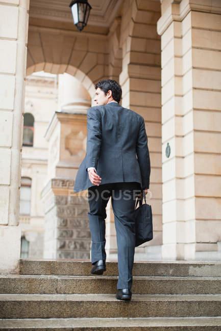 Homme d'affaires escalade étapes de la construction — Photo de stock
