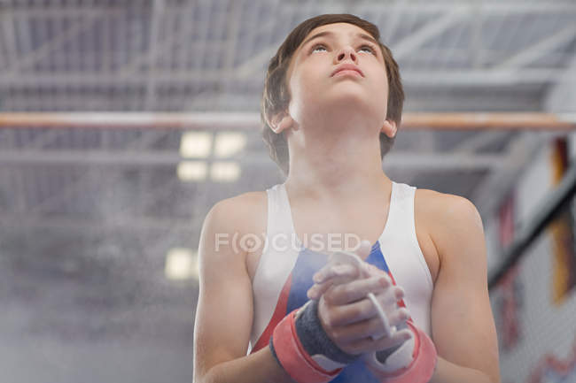 Gymnast rubbing sports chalk onto his hands — Stock Photo
