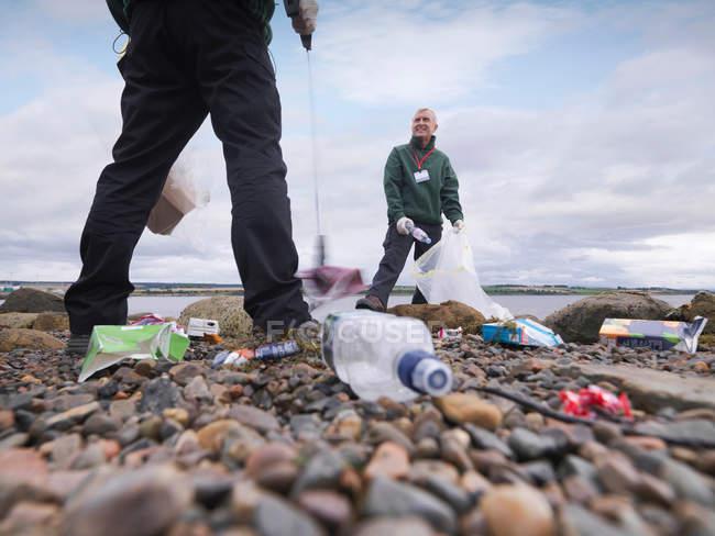 Двоє чоловіків екологів видалення сміття з берега моря — стокове фото
