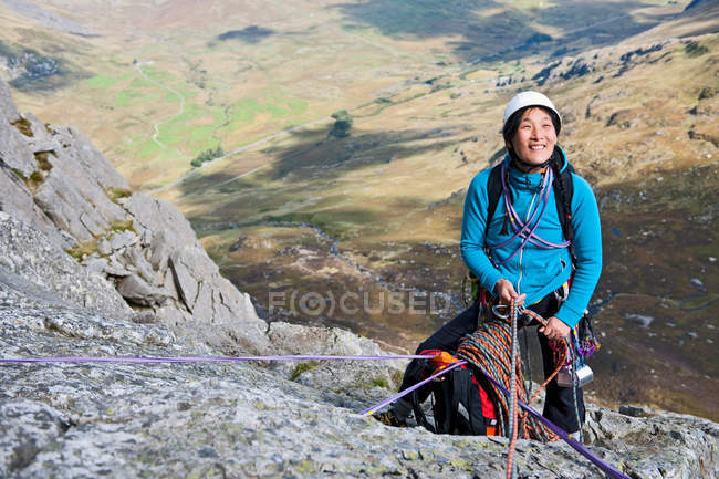 Female rock climber at an anchor point and belaying — Stock Photo