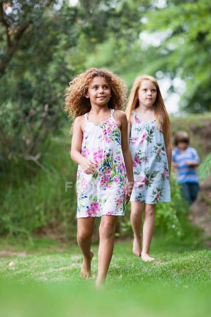 Дівчата, які ходять в траві разом, хлопчик у фоновому режимі — стокове фото