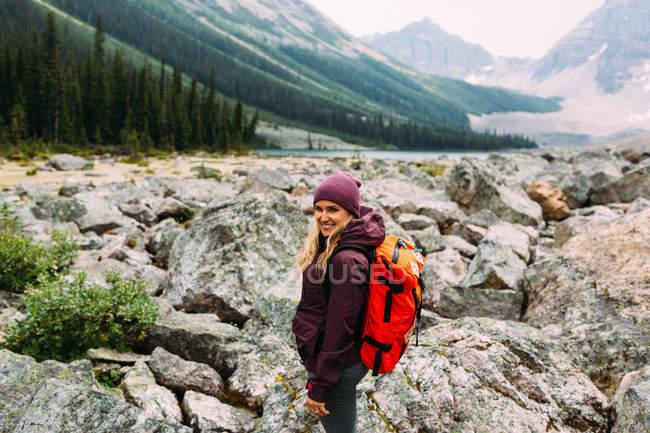 Vista laterale della donna adulta sul paesaggio roccioso che trasporta lo zaino guardando la fotocamera sorridente, Moraine Lake, Banff National Park, Alberta Canada — Foto stock