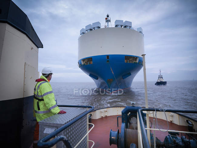Tug worker on deck of tug looking at ship out to sea — Stock Photo