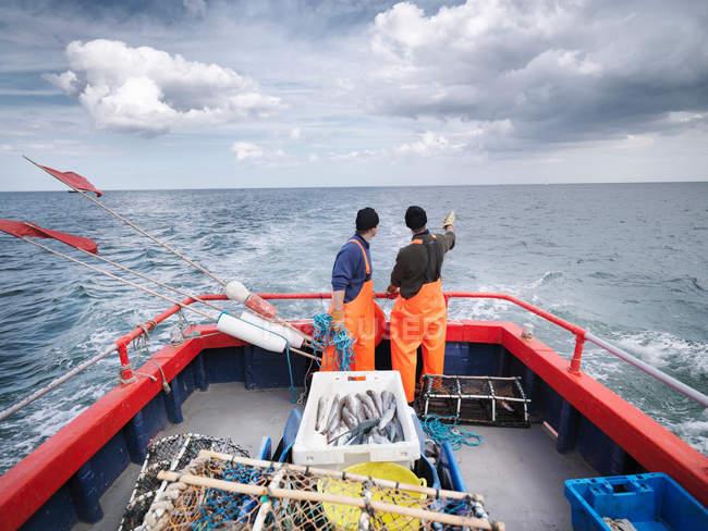 Pêcheurs sur le bateau indiquant vers la mer — Photo de stock
