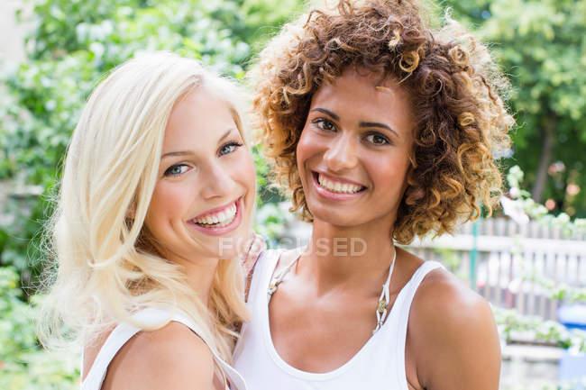 Lächelnde Frauen, die zusammenstehen — Stockfoto