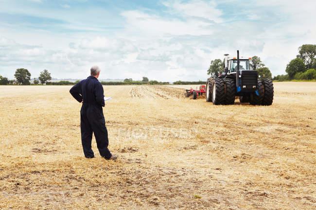 Farmer overlooking tractor in crop field — Stock Photo