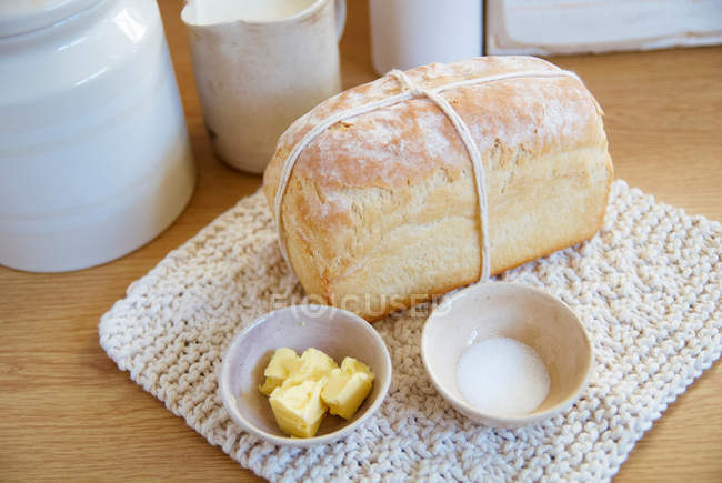 Loaf of bread with butter and salt in bowls — Stock Photo