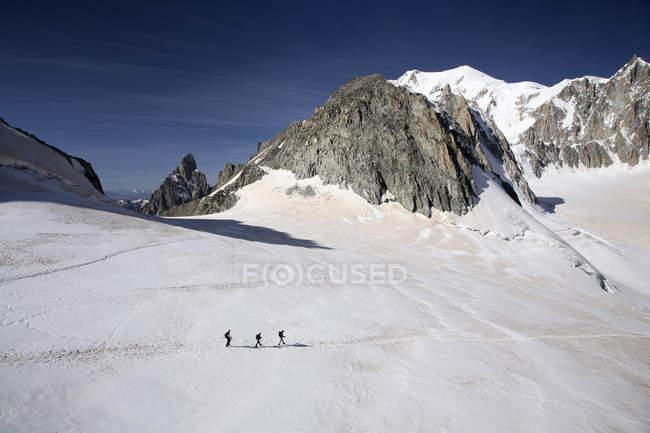 Tres excursionistas en las montañas de invierno - foto de stock