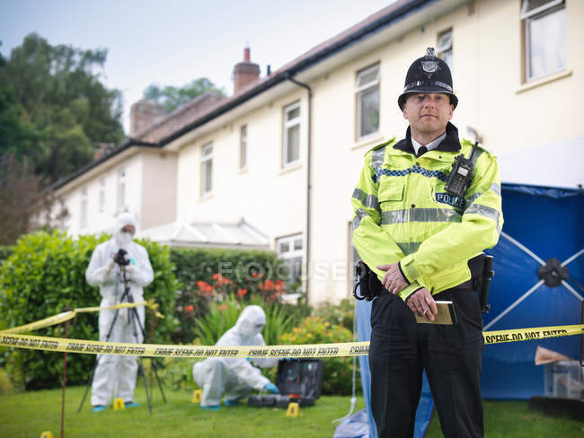 Portrait of policeman at crime scene, forensic scientists outside house in background — Stock Photo