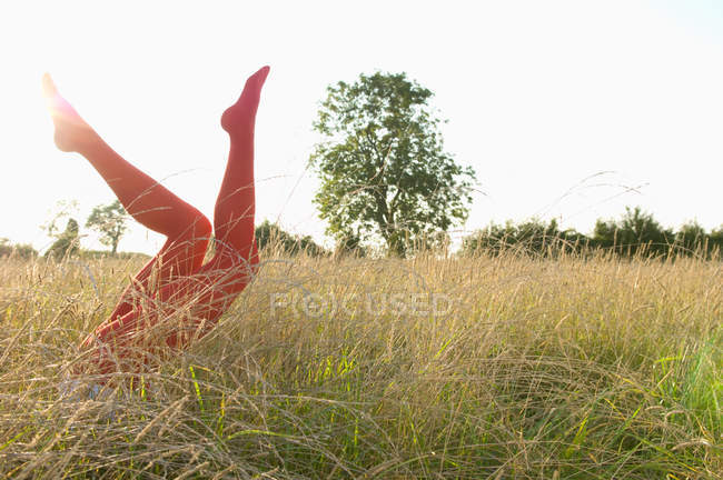 Female legs wearing red tights raised up on field — Stock Photo