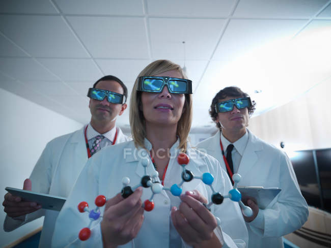 Three scientists in lab coats wearing 3D glasses and holding molecular model — Stock Photo