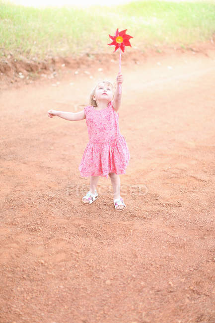 Girl playing with pinwheel on dirt road — Stock Photo