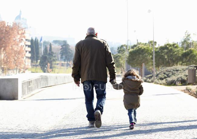Vue arrière du grand-père et de la fille marchant dans le parc — Photo de stock