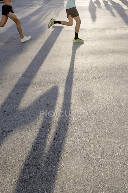 Ноги двох чоловіків бігають по дорозі — стокове фото