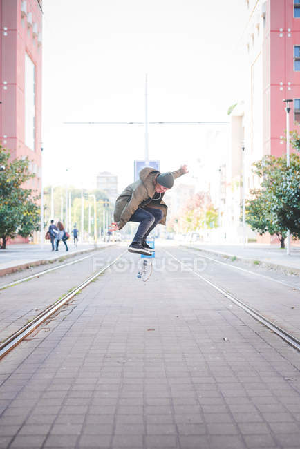 Young male skateboarder doing skateboarding jump on tramway — Stock Photo