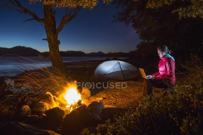 Woman looking at her laptop by a campfire at Nahuel Huapi Lake in Patagonia — Stock Photo