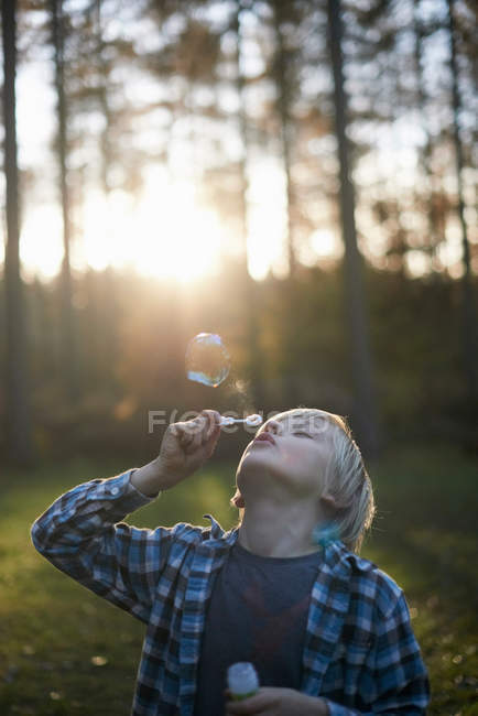 Boy blowing bubbles in forest in backlit — Stock Photo