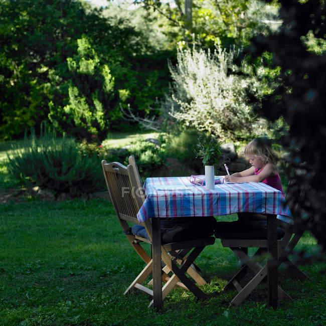 Ragazza che disegna a tavola all'aperto — Foto stock