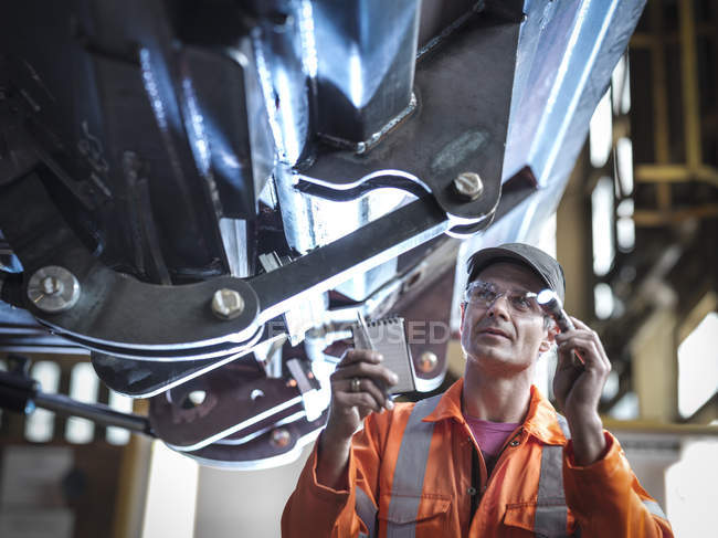 Ingénieur utilisant la torche pour vérifier le travail en usine — Photo de stock