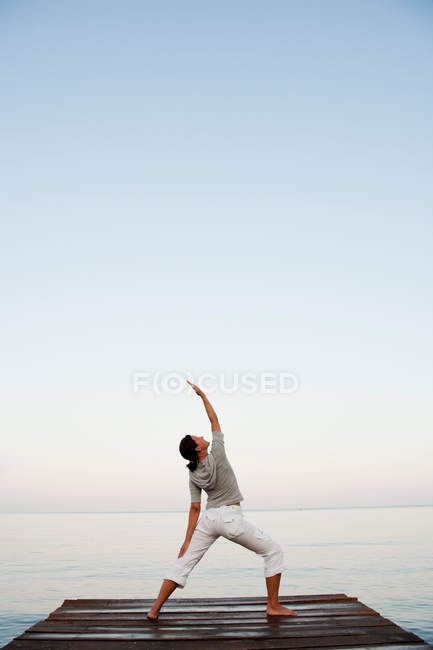 Young Woman Doing Yoga At Jetty — Stock Photo