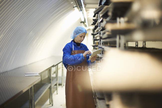 Female worker updating digital tablet whilst preparing stack of seed trays in underground tunnel nursery, London, UK — Stock Photo
