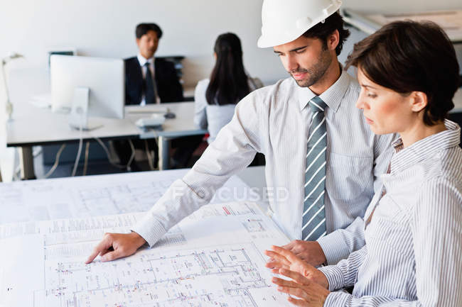 Business people reading blueprints — Stock Photo