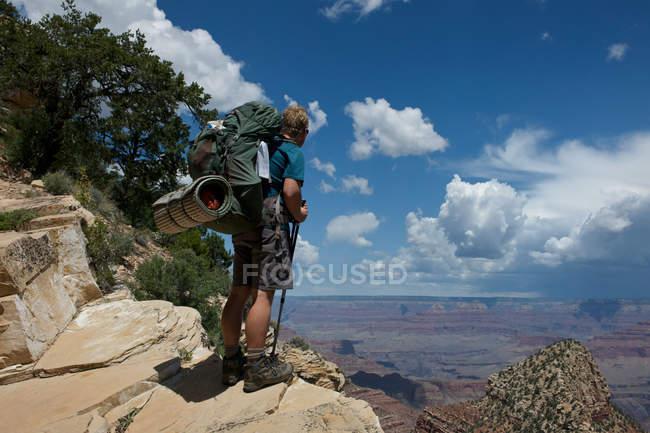 Hombre de pie sobre rocas, New Hance, Grandview Hike, Gran Cañón, Arizona, Estados Unidos - foto de stock