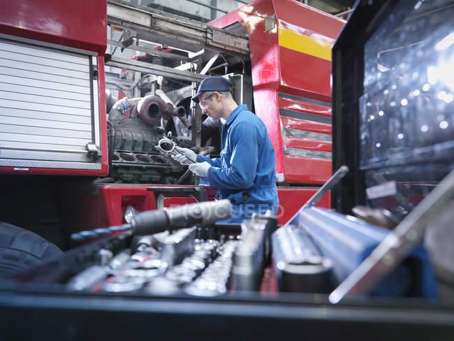 Інженер, що працює на движку в авторемонтної фабрики — стокове фото