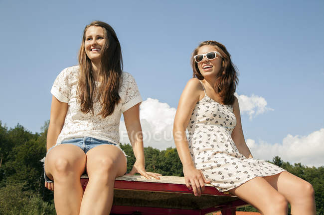 Two young women sitting in trailer, low angle view — Stock Photo