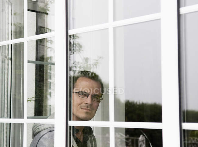 Portrait of mid adult man looking out of window — Stock Photo