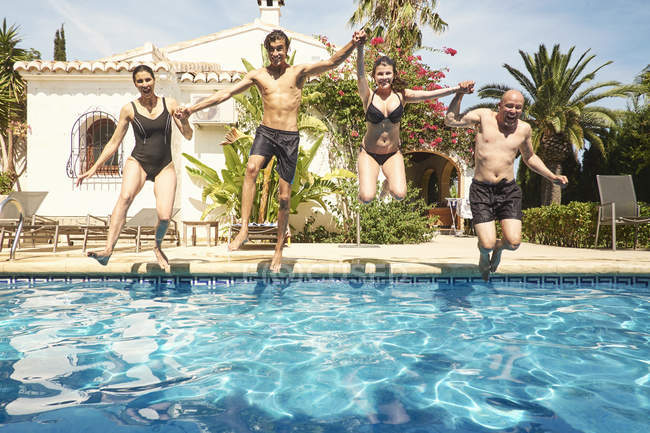 Mature couple holding hands with son and daughter jumping into in swimming pool — Stock Photo
