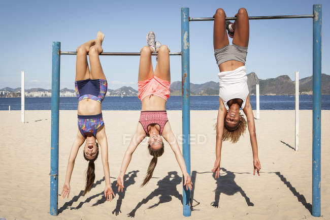 Three young women hanging upside down from bar on beach — Stock Photo