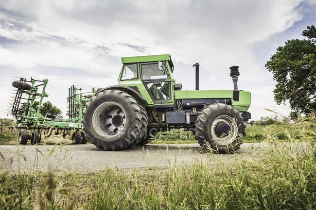 Fermier conduisant le tracteur sur une route rurale — Photo de stock