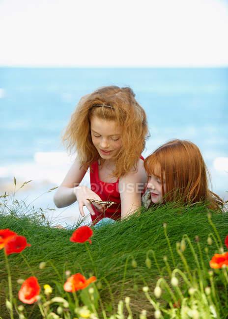 2 girls watching butterfly — Stock Photo