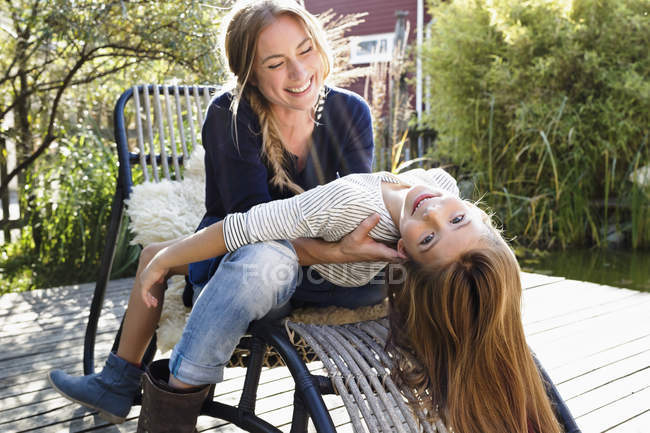 Girl sitting on mother's lap, leaning back — Stock Photo