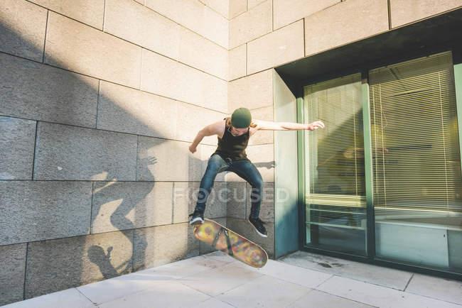 Jeune skateur urbain mâle faire truc de saut skateboard en coin — Photo de stock